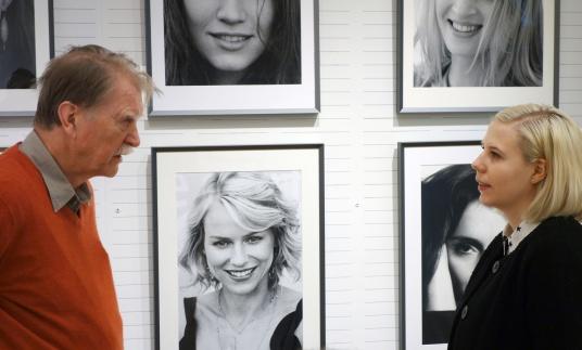 Kurirens Sofie Lind lyssnar på Leif-Erik under hängningen av hans utställning. Foto: Kjell Hjort