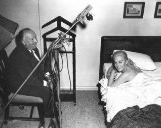 Kim Novak får regiinstruktioner av Hitchcock i scenen när hon vaknar upp i James Stewarts lägenhet i Studie i brott
