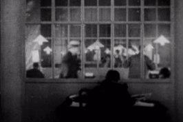 Hitchcock (med ryggen mot kameran)  i sin första cameos i The Lodger