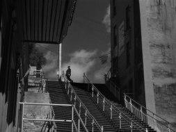 Hitchcock passerar ovanför en trappa i början av filmen