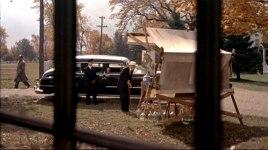 Hitchcock passerar förbi en bil till vänster i bild