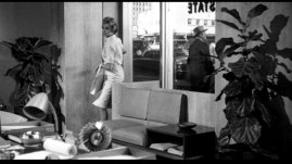 Hitchcock står utanför kontorsföntret 4 minuter in i filmen