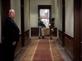 Hitchcock kommer ut ur en dörr efter att Marnie passerat förbi