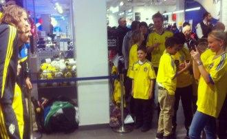 Eventpersonal från Renommé tar foton på fans med fotbollspelare från Svenska landslaget.