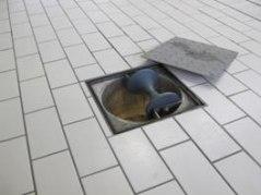 Linbrunn i golv. Denna linbrunn är försedd med ett uppfällbart hjul för att underlätta nedtransport av linan till källaren.