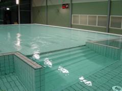 Integrerad trappa som leder från bassäng med fast golv till bassäng med höj- och sänkbart golv.