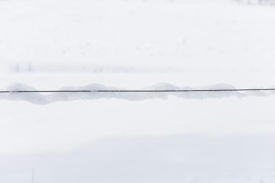 Snö som hänger på sidan av en ståltråd. Konstigt hur den kan hänga kvar...