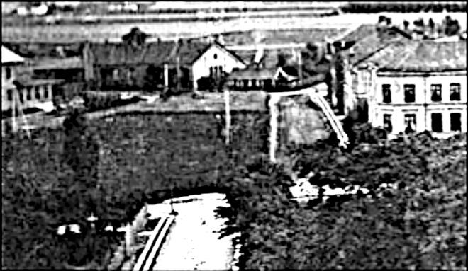Delförstoring: Liten stuga som ligger exakt där den allra äldsta plankorsningen låg för Öm-vägen. Trolig banvaktsstuga, som kan ha flyttats från sin plats vid sidan av Verkstaden. (Skövde Stadsmuseum)