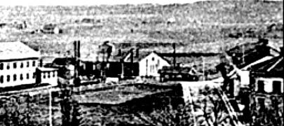 1895 med lokstall och gamla Öm-vägen som korsar mellan lokstall och Verkstad -troligen avstängd för allmän trafik? OBS! Den lilla stugan - troligen flyttad banvaktsstuga. (Skövde Museum)