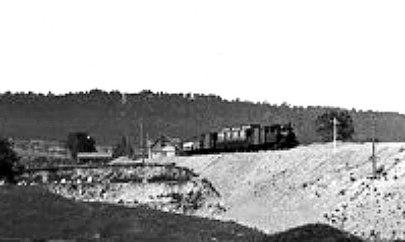 Ännu närmare ser man stugans utformning med Billingsberget i bakgrunden och de ekonomibyggnader som låg norr om Varnhemsvägen och väster om SAJ-banan.