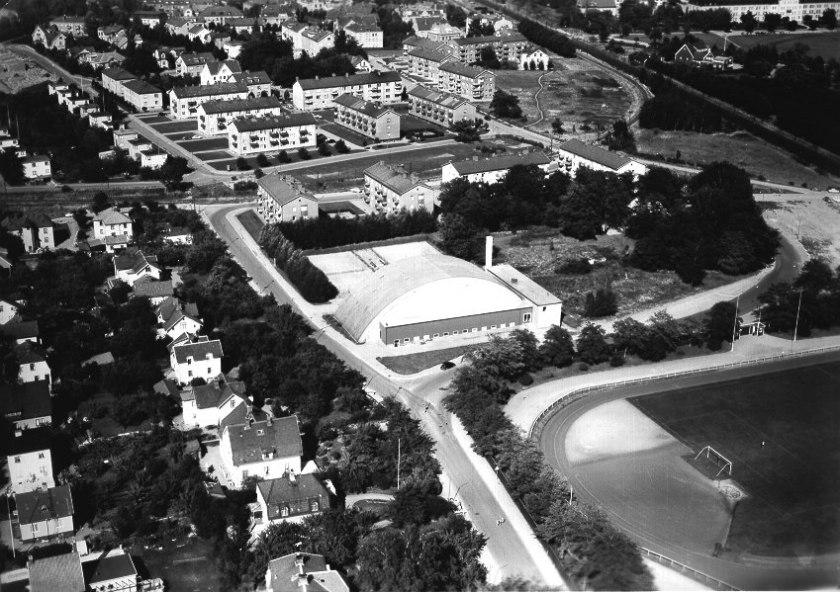 1950-talet efter nyss uppförd idrottshall. SAJ svänger ut från stambanan alldeles efter Vasaplan och passerar Skaraborgsgatan. (Skövde Stadsmuseum)