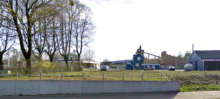 Träden stod söder om Varnhemsvägen och gick mitt i bilden med SAJ-korsningen där bilen står. Den gamla stugan t h är kvar sedan SAJ-tiden.