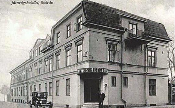 1920-30-talet krävde sin modernisering och fasaden med ny entré fanns på plats. Staketet mot Kyrkogatan borttaget. Bilismens inträde i form av en Ford parkerad på Mörkegatan. (Skövde Stadsmuseum)