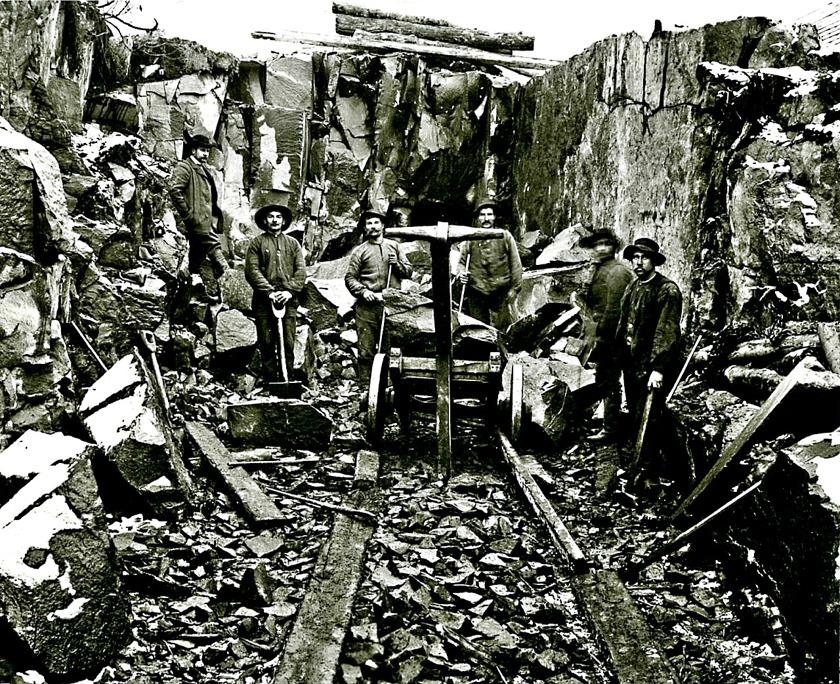 """Nordväst om Våmbs kyrka arbetar ett av kalknedbrytningslagen med att skapa det djupa """"dike"""" som krävdes för att tåget skulle orka ta sig upp och klara stå emot nedförslöpan mot staden. (Skövde Stadsm"""