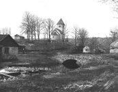 Våmbs kyrka 1890-talet med bron från södra till norra sidan av Våmbobäcken. (Bild Skövde Stadsmuseum - nummer: 105261).