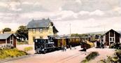 Varnhems järnvägsstation 1904 med lok Nr 1, Axvall, i tåg mot Axvall samt lastning vid lastkaj. Snett emot stationen bakom träden ligger Junkragården. Lägg märke till SAJ-staket framför träden.
