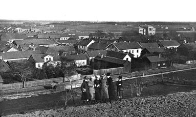 En bild från sydvästra Skövde. I bakgrunden ses Kungsgatan 5 uppfört 1879 och Skolgatan 4 är under uppförande och året är då 1884. (Skövde Museum)
