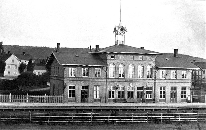 Järnvägsstationen 1870 med ursprungligt staket för Västra stambanan och Borgmästare Wetterbergs Villa i bakgrunden där nu Hotell Billingen ligger. (Bild från wwww.vykort.panatet.se)