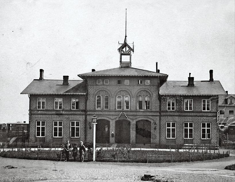 """Tidigt 1870-tal med Vattenkur och järnvägsvagnar i bakgrunden och en """"rundel"""" med relativt nyplanterade växter i fonden. (Bild Skövde Museum)"""
