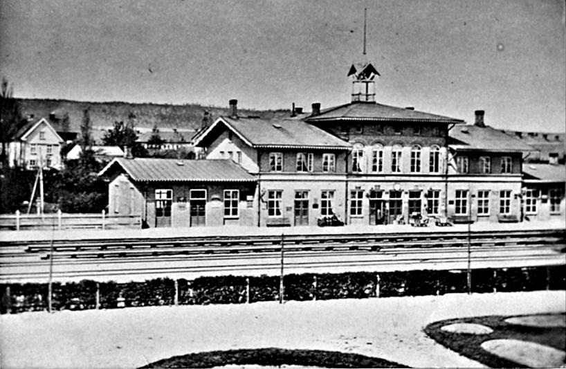 """Järnvägsstationen 1878 två år efter Karlsborgsbanans etablering. Nu utbyggd med två """"flyglar"""". Utökad bangård med fler spår och träperronger. (Bild Skövde Stadsmuseum)"""
