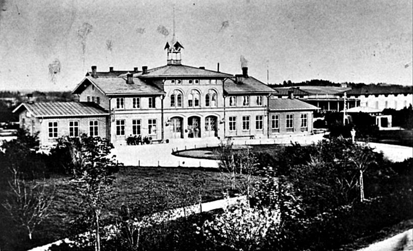 Järnvägsstationen 1878 med norra delen av Järnvägsparken. Sparsam gasbelysning gjorde grusgångarna belysta nattetid och mycket grönska har planterats. (Bild Skövde Museum)
