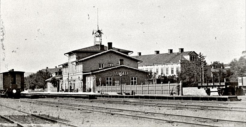 Järnvägsstationen 1880 med blivande Järnvägshotellet (1913) längst bort i bild och Rådman Petterssons/Grönvalls hus (revs 1950-talet) samt del av norra lastkajen.  (Bild Skövde Stadsmuseum)