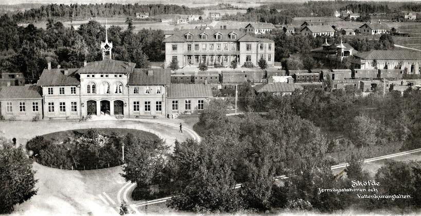 Järnvägsstationen 1889 med Vattenkuranstalt och omgivande landsbygd österut. Gjutargärdet med Verkstadens relativt nyuppförda arbetarbostäder syns bakom Vattenkurens Societetshus. (Skövde Stadsmuseum)