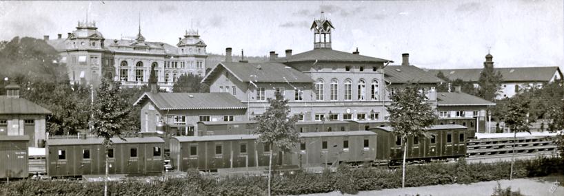 Järnvägsstationen tidigt 1890-tal med Hotell Billingen i bakgrunden. Foto från Vattenkuranstaltens nu mer uppväxta trädgård med trädplantering. Grönskan har blivit påtaglig. (Skövde Stadsmuseum)