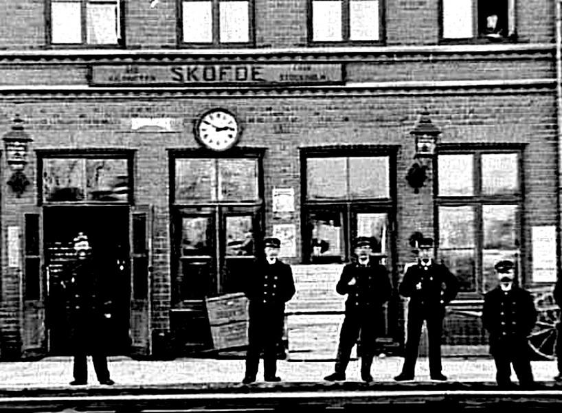 """Det alltigenom mustaschprydda """"stationsgardet"""" år 1900, med en station full av aktivitet. Lådor, affischer, tidtabeller och dragkärra - upplysta kvällstid av gaslyktor på fasaden. (Västergötlands Muse"""