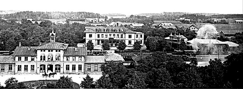 """Järnvägsstationen 1902 med kusk och hästskjuts, Vattenkuranstalt, Societetspaviljongerna, """"Gjutaregärdet"""" med Mekaniska Verkstadens arbetarbostäder. (Bild Skövde Stadsmuseum)"""