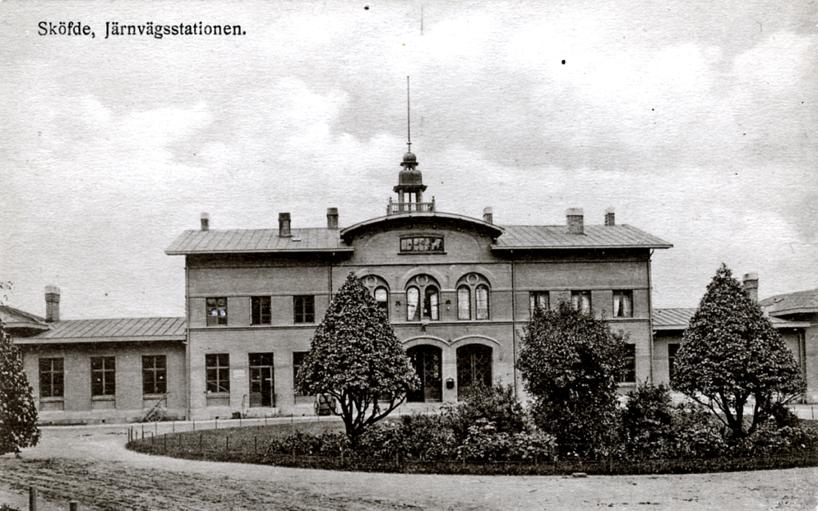 Efter 1906 och stationen är rejält ombyggd, med tilläggsvåning under det höjda och välvda taket och en enhetlig fasad. Växtligheten formklippt och nygrusad plan. (Skövde Stadsmuseum)