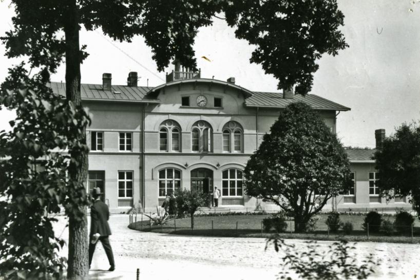 1910 med bibehållen formklippning av växtligheten, monterad elektrisk urtavla i övre fönsterraden med ändrad fönsterkarm. (Skövde Stadsmuseum)