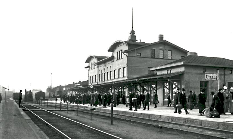 Nu har resandefrekvensen ökat ytterligare och stationen sjuder av liv inför det ankommande tåget från Göteborg mot Stockholm. Det är den 1 juli 1915, kl. 11.05. Dokumenterat av Ludvig Ericson, Skövde