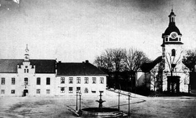 1870-tal med ombyggt rådhus. Kyrkan ännu inte ombyggd (1890) och gjutjärnsfontänen pryder torget med gaslyktor. (Skövde Stadsmuseum)