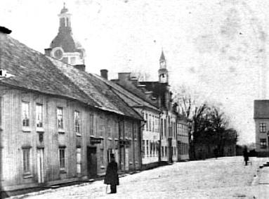 Bild från 1870-tal med Rådhusgatan - då Norra Storgatan ut mot Mariestad - Hjo hitåt i bilden. (Västergötlands Museum)