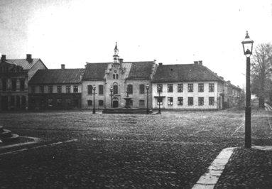 1880-tal. Bild från väster med rådhuset, skolhuset i fonden, gjutjärnsfontänen och gaslyktor. (Skövde Stadsmuseum)