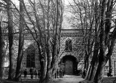 1880-tal. Kyrkans fasad innan renovering med puts och sandsten. Lejonporten i söderläge. (Skövde Stadsmuseum)