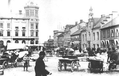 Sekelskiftesbild. Torgdag ända ut på Rådhusgatan med vagn- och hästparkeringar. Mycket kreatur! (Skövde Stadsmuseum)
