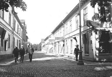 S:t Sigfrids gata i solljus och finklädda herrar. En riktig shoppinggata när det begav sig! (Skövde Stadsmuseum)