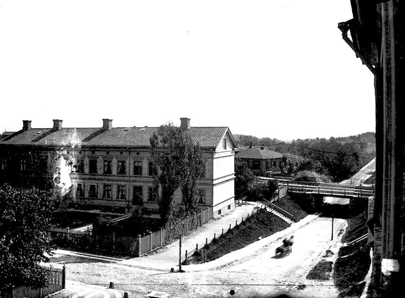 """Undergången före SAJ-bron med """"Gejierska huset"""" (Järnvägshotell 1913), Mörketrappan, Vattenkurens Societetssalong, Öm-vägen och Jungfrukällan i slänten t h i bild. (Skövde Stadsmuseum)"""