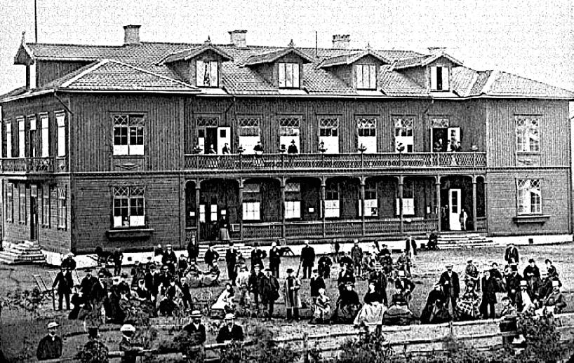 Något år efter starten med gäster och personal framför 1859 års staket för Västra stambanan mot bangården. Kanske var en järnvägsvagn plattform för fotografen? (Skövde Stadsmuseum)