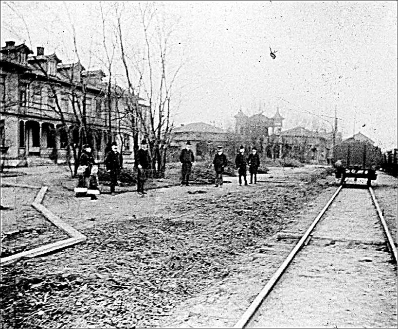 Här har man byggt både Societetssalonger/sommarpaviljonger och fått trädgården naggad av vidgad bangård någon gång 1876-77. Staketet borta.(Skövde Stadsmuseum)