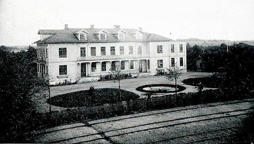 1880-tal med utbyggd huvudbyggnad åt söder, badkontor och paviljonger som knappt syns i trädskuggan.  (Skövde Stadsmuseum)
