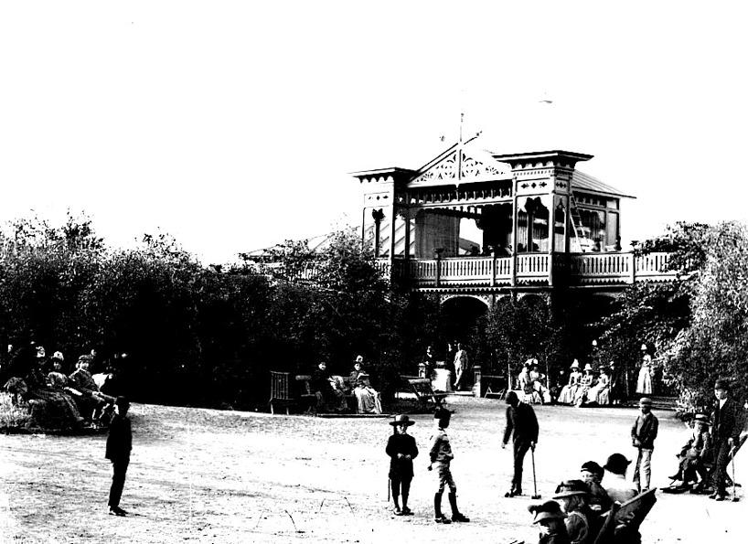 """Porten in i Salongerna är imponerande och fylld med """"snickarglädje"""" och torn. Gästerna flanerar och sitter på bänkarna och njuter någon gång på 1890-talet. (Skövde Stadsmuseum)"""