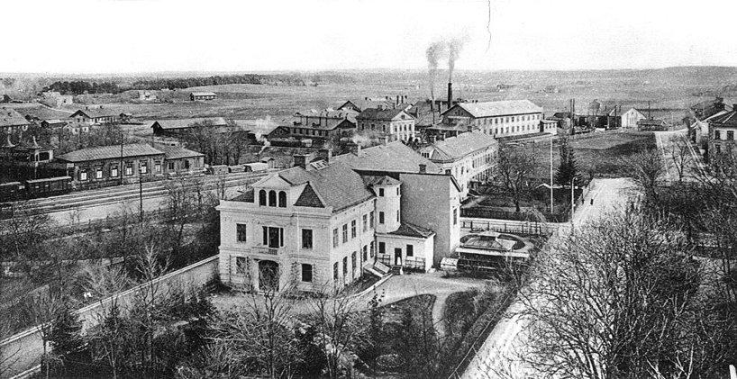 """1895. Stambanan söderut med Mörke-, Trädgårds-, Kyrko- och Kungsgatorna, undergång, Societetssalongerna, arbetarbostäderna på """"Gjutaregärdet"""", Verkstaden och lokstall. (Skövde Stadsmuseum)"""