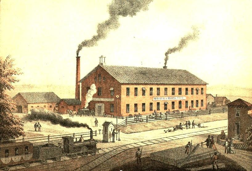 """Litografi 1860-talet. Xylografi 1868. Byggnadsår Verkstad - då """"John G. Grönvall & Co"""". Bilden tidstypisk och byggnader, staket, markområde, mm stämmer med kartor och övr bilder. (Skövde Stadsmuseum)"""