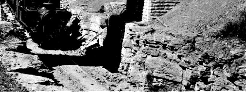 """Del av bild där ett av tågen passerar i """"diket"""" strax efter byggnationen. Man kan se att det inte är särskilt väl """"städat"""" ännu från ras och sten. (Skövde Stadsmuseum)"""