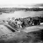 Flygfoto av Västgöta-lägret, Axvalla hed taget under Flygskolans verksamhet 1912.  Obs flygplanet på marken i bakgrunden. Garnisonsmuseet 1078-531