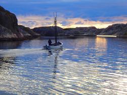"""1. Jette Gustafsson, Tullboden. Juryns motivering: """"Bilden visar den traditionella fiskebåten i den exotiska bohuslänska naturen och samtidigt har det unika ljuset fångats vilket ger en fantastisk helhet. Vågorna i förgrunden speglar färger från himlen i bildens bakgrund och på så sätt uppvägs bildens mörka partier som därmed skapar en ljus bild. En välbalanserad avvägning med den mycket diskreta kanten av det röda sjömärket i bildens vänstra mitt balanserar kompositionen."""""""
