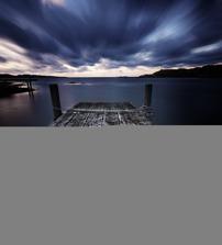 """2. Claes Thorberntsson, Makrillviken på Smögen. Juryns motivering: """"En skicklig komposition som blandar flera viktiga element. Det lugna havet som likt en spegel både tar kolorit och ljus från himlen. Havet inger stilla lugn och molnen ger i motsats till havet en dynamik som gör att bilden får en spännande mystik och inbjuder betraktaren till att studera fotografiet i detalj. Kompositionen med dess många mörka blå nyanser uppvägs och förstärks av lövets starka varma kolorit på den ljusa bryggan."""""""